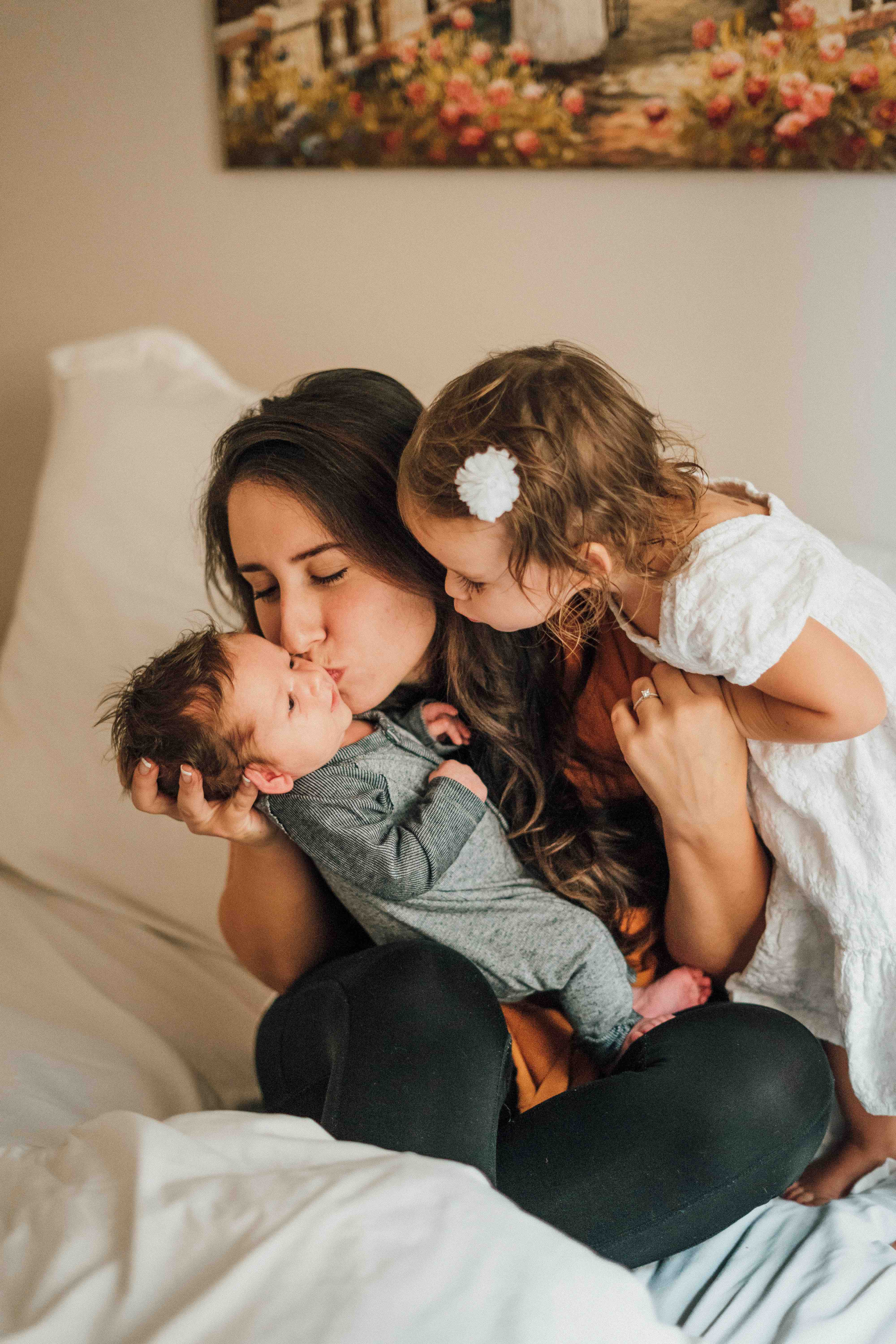 Mother kissing baby with daughter leaning over her